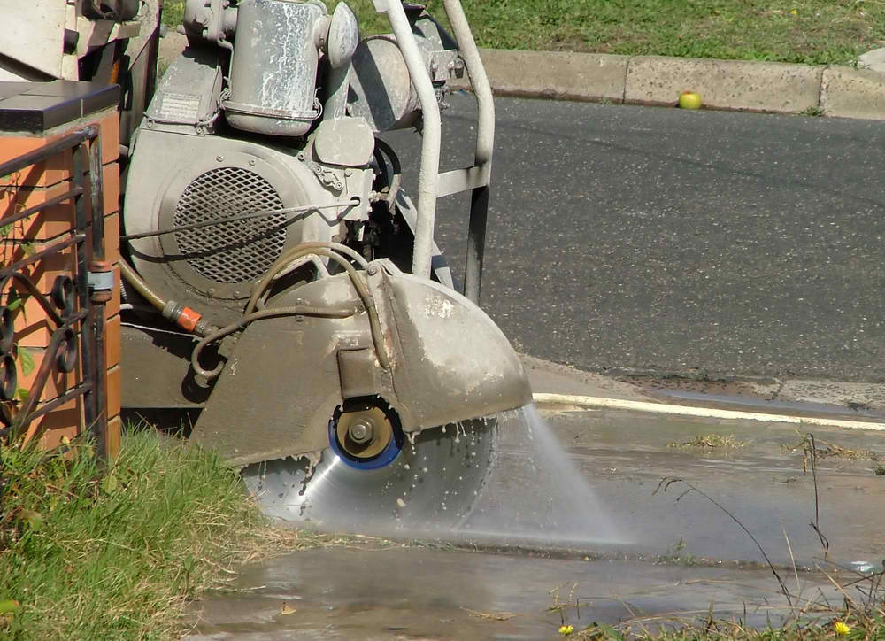 man cutting concrete road