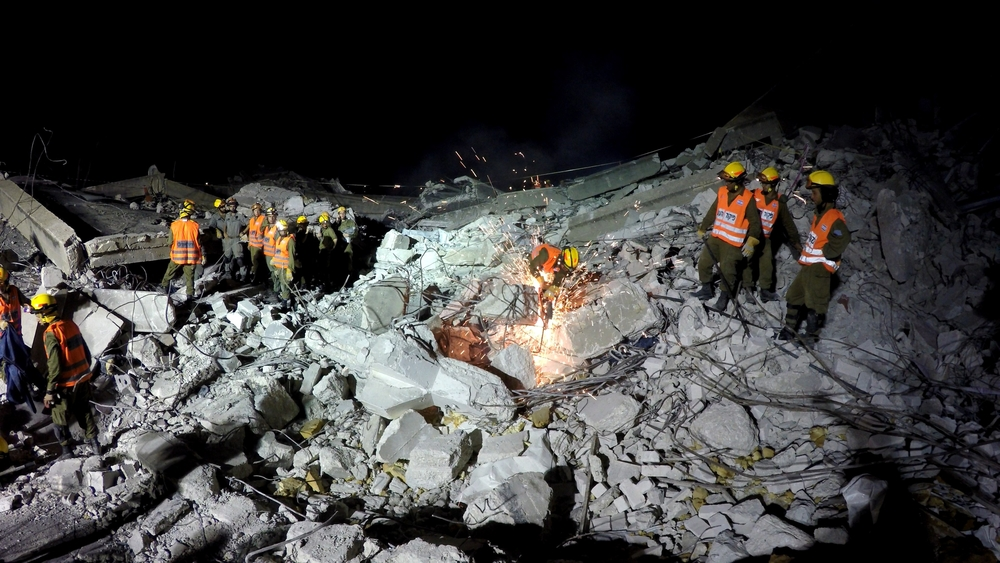 rescuers on earthquake rubble